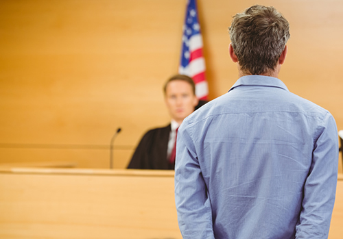 Man in Handcuffs Standing in Front of a Judge in a Courtroom