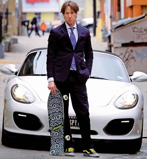Rob Buford Standing in Front of a Sports Car Holding a Skateboard 