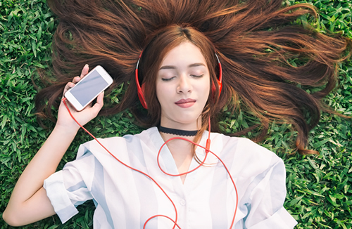 Picture of Woman Laying on Grass Wearing Earbuds