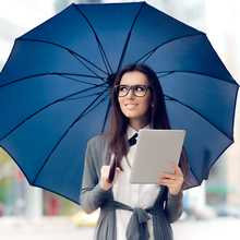 A Businesswoman Holding an Open Umbrella in One Hand and an Ipad in 