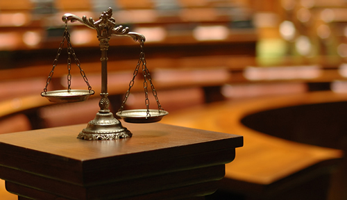 Scales of Justice on a Desk in a Courtroom