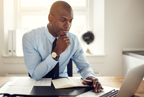 Business Man Sitting at His Office Desk Working on His Laptop