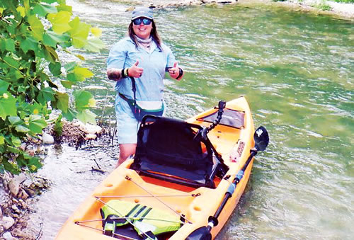 Picture of Libby Ferguson Standing Next to her Kayak