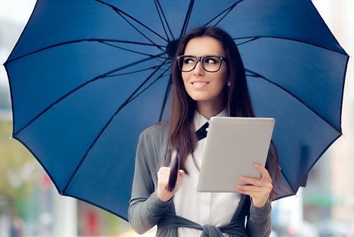 Woman Holding an Umbrella in one hand and an iPad in another