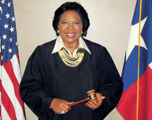 Picture of retired chief justice carolyn write standing in front of    the american and texas flags and holding a gavel in her hands